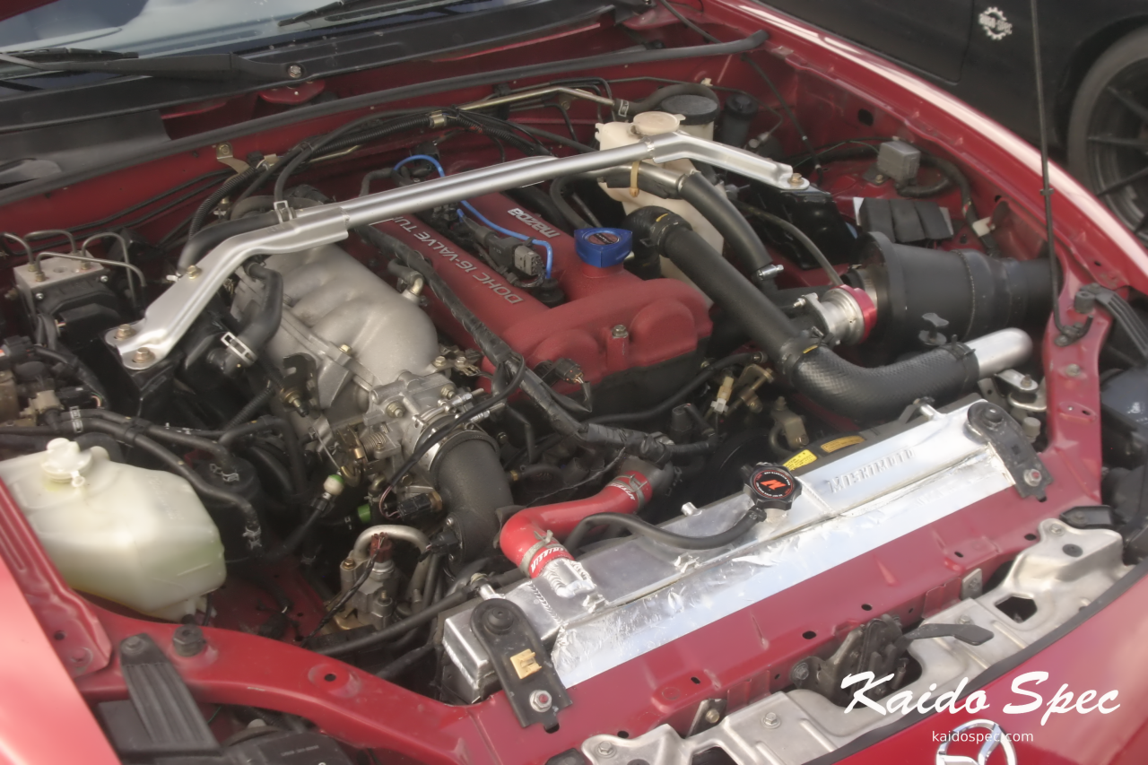 "The engine bay of the above Mazdaspeed.  Featuring what the community calls ""Joes Intake"" after the creator, a larger front mount intercooler, and Mishimoto radiator."