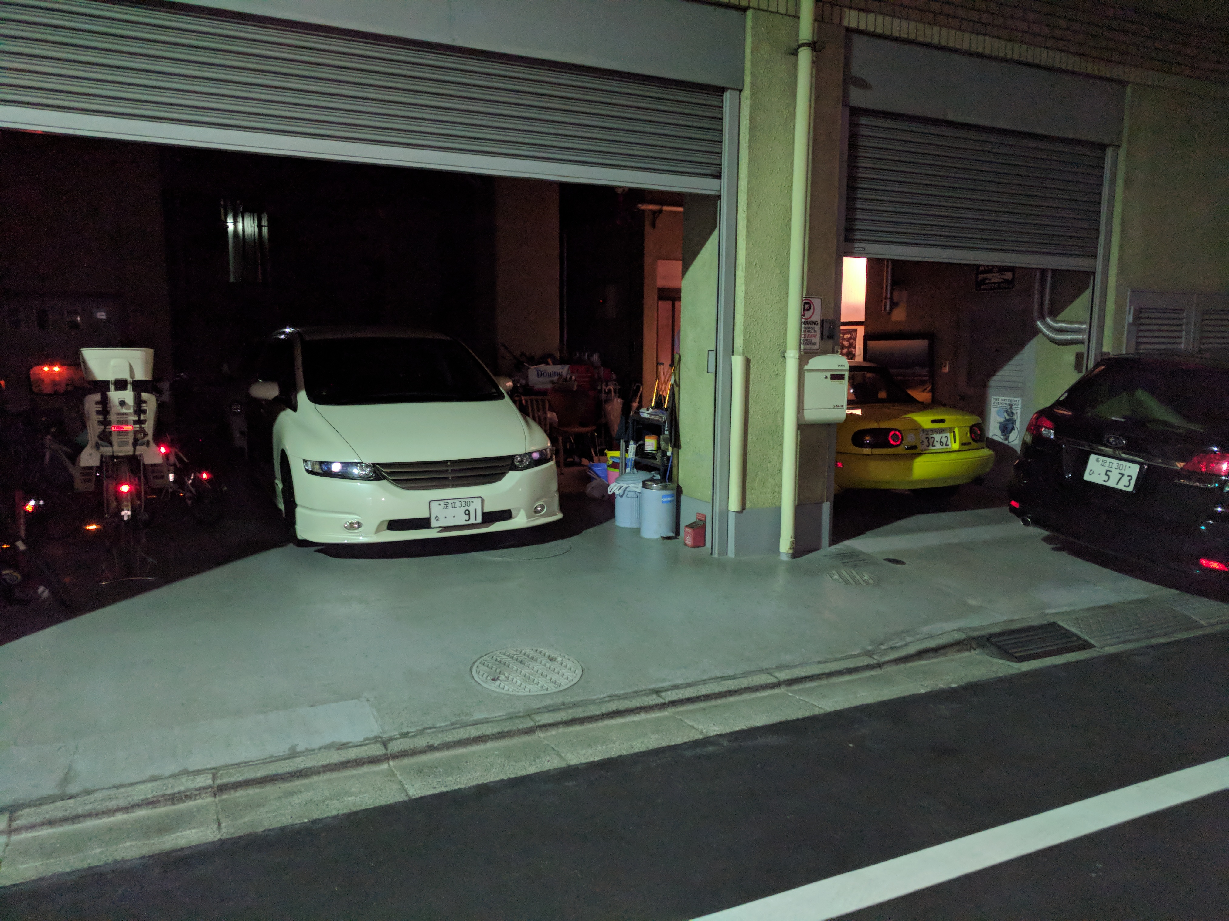 Moments after leaving my apartment for the first time to explore the area, I spot a  lowered minivan and a yellow NA Roadster in the same garage.